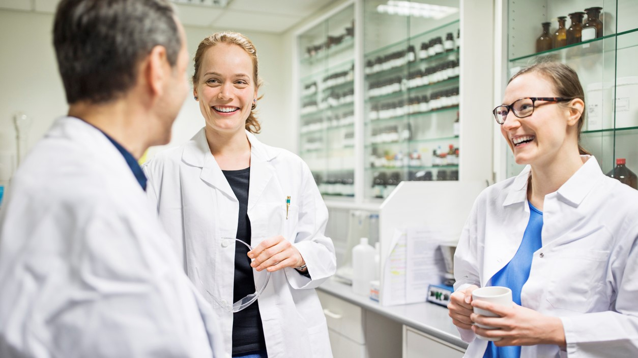 Happy scientists talking in laboratory. Smiling male and female pharmacists are wearing lab coats. Professionals are at pharmacy.